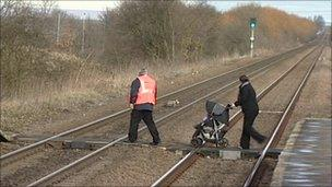 A woman being helped across the tracks at Doncaster's Thorne North station
