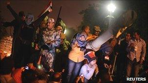 Egyptian protesters celebrate with soldiers on top of a tank in Tahrir Square, Cairo, 11 February 2011