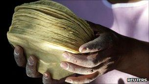 Woman holding a pile of corn tortillas