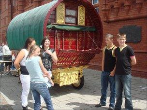 Young Gypsies and Travellers with a traditional caravan