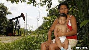 Maria Eugenia Briceno and her son sit in front of her house which is just in front of an oil well in Lago Agrio, Ecuador, January 2011