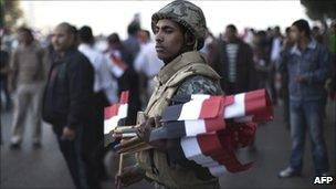 An Egyptian soldier greets demonstrators with national flags as they pour into Cairo's Tahrir Square for celebrations on 18 February 2011