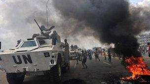 UN peacekeepers drive past supporters of Alassane Ouattara as they demonstrate in the Abobo neighbourhood in Abidjan on 19 February 2011