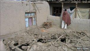 Man stands in ruins of house relatives say was destroyed after an air strike in Nangarhar province February 21, 2011