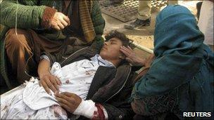 A mother touches her wounded son after a suicide attack in Emam Saheb district of Kunduz province February 21, 2011