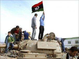 A man holds a pre-Gaddafi Libyan flag on top of a tank in Benghazi (21 February 2011)