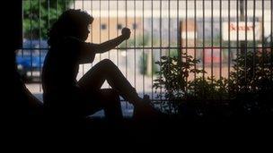 young girl sitting near railings