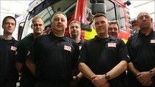 Some of the firefighters standing in front of a fire engine