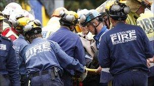 Rescue workers tend to a woman as she is lifted clear of the wreckage of the collapsed Pyne Gould Corporation (PGC) building, 23 February 2011