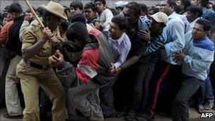 An Indian policeman uses a bamboo stick to beat back cricket fans outside Bangalore's Chinnaswamy stadium on 24 February 2011