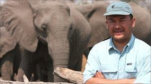 Jose Cortes standing in front on herd of elephant