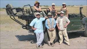 Group of people in front of a four-wheel drive vehicle
