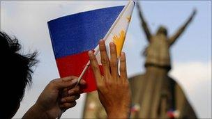 A student waves a miniature Philippine flag during a re-enactment of the 1986 People Power revolt at the People Power Monument in suburban Manila on 24 February 2010