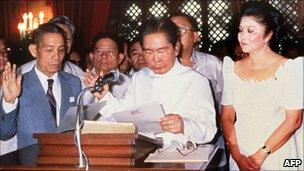 Ferdinand Marcos takes the oath of office on 24 February 1986 in Manila while his wife Imelda looks on