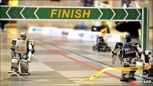 Robovie-PC (right) crosses the finish line in the world's first full-length marathon for two-legged robots in Osaka, Japan, 26 February 2011