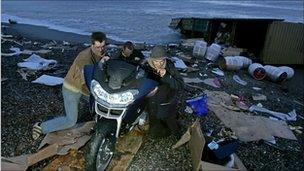 People taking a motorbike off the beach