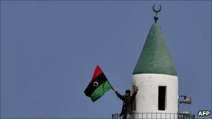 A Libyan rebel waves a pre-Gaddafi Libyan flag in the town of Bin Jawad (27 March 2011)