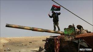 A rebel fighter walks on a tank along the road between Ajdabiya and Brega, 6 April