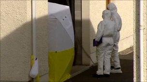 Forensics officers examine garage where arms were found