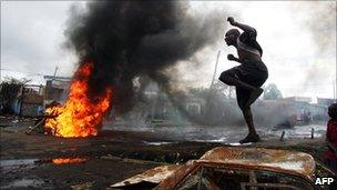 Man jumps on a burnt vehicle in Nairobi, Kenya, on 16/1/2008, during unrest that followed the disputed 2007 election