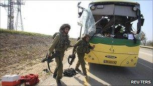 Israeli soldiers run past a bus hit by a mortar, southern Israel (7 April 2011)