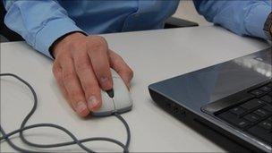 man using mouse and computer