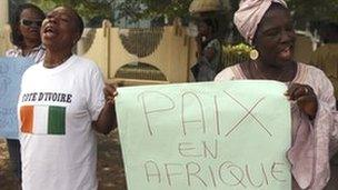 """Women protest outside the ECOWAS headquarters in Abuja. A placard reads """"peace in Africa"""""""