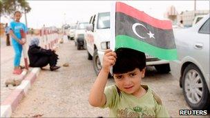 Boy holds an old Libyan flag - symbol of the rebels - at the Dehiba border crossing (8 May 2011)