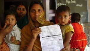 A woman in Bihar shows the document which entitles her daughter to state benefits