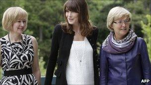 French President Nicolas Sarkozy's wife, Carla Bruni-Sarkozy (C) poses with Laureen Harper (L), wife of Canadian Prime Minister Stephen Harper and Geertrui Van Rompuy-Windels, wife of European Council President Herman Van Rompuy, prior to a working lunch at the Villa Strassburger on the sidelines of the G8 summit in Deauville, western France, on Thursday
