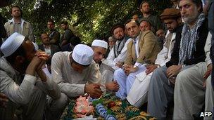 Former Afghan Foreign Minister Abdullah Abdullah (R) sits near the coffin of slain police chief, Gen Mohammed Daud Daud