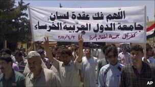"""Mobile phone photo of a protest in the northern Syrian town of Idlib. Banner reads: """"May God help break the silence of the Arab League"""" (3 June 2011)"""