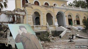 A poster of Libyan leader Gaddafi is seen in front of a government building damaged by coalition air strikes, according to the government, in Tripoli
