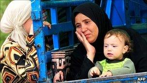 Syrian women who fled the unrest in Syria wait at a makeshift camp in the northern city of Idlib, near the Turkish village of Guvecci in Hatay, on 13 June 2011