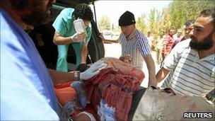 A wounded Libyan rebel fighter is put into an ambulance west of Misrata (17 June 2011)