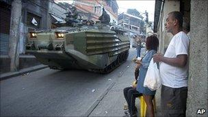 Residents look out from a shop entrance as Brazilian marines pass in an armoured vehicle, Mangueira, Rio de Janeiro, Brazil (19 June 2011)