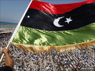 A man waves a pre-Gaddafi Libyan flag in Benghazi (17 June 2011)