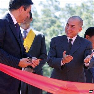 Cambodian King Norodom Sihamoni, right, introduces French Prime Minister Francois Fillon, left, cut a ribbon at a temple, northwest Phnom Penh, Cambodia, July 3, 2011