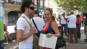 MartizaRodriguez holding a sign saying 1 x 2