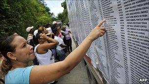 A relative of an inmate of El Rodeo I penitentiary points at a name on the list of inmates, in Guatire, outskirts of Caracas, June 21, 2011.