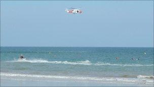 The Portland Coastguard helicopter assisting the RNLI at Boscombe beach, Bournemouth