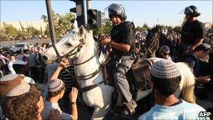 Mounted police officer surrounded by religious Jewish demonstrators outside Supreme Court.