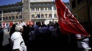 Pensioners stand outside the Italian parliament after a demonstration on 15 July 2011 in Rome.