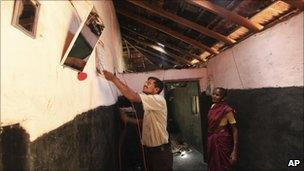 In this May 24, 2011 photograph, Parvin Yeyyada works with electric wiring as Boommi Gowda looks on during the installation of solar power in her house in Nada