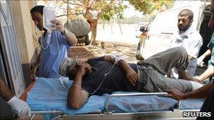 An injured fighter is taken into hospital in Misrata, Libya (6 July 2011)