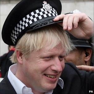 London Mayor Boris Johnson wears a policeman's hat in Trafalgar Square
