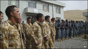 Soldiers from New Zealand (L) part of the Nato- led International Security Assistance Force (Isaf) stand on a line with Afghan policemen during handover control for security in Bamiyan