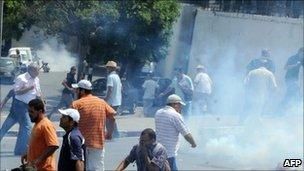 Demonstrators and a cameraman run for cover after tear gas was used by Tunisian security forces to disperse them in La Kasbah square, on July 15, 2011.
