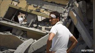A man looks at a house that Libyan officials say was bombed by Nato forces, killing two children and their mother near Zlitan