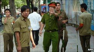 A policeman tries to stop a foreign journalist taking pictures as they guard the Ho Chi Minh City People's Court